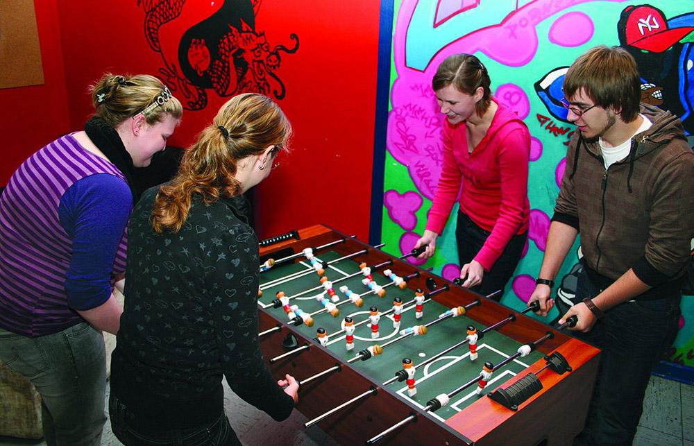 Jugendliche spielen am Kickertisch im Jugend-und Begegnungszentrum Barßel.