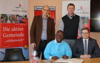 Bürgermeister Nils Anhuth (von rechts) und Erster Gemeinderat Michael Sope begrüßten Pastor Samuel Nyohnyoh, der vier Wochen Gast von Pastor Thomas Perzul sein wird, im Rathaus. Bild: Gemeinde Barßel/Bergmann