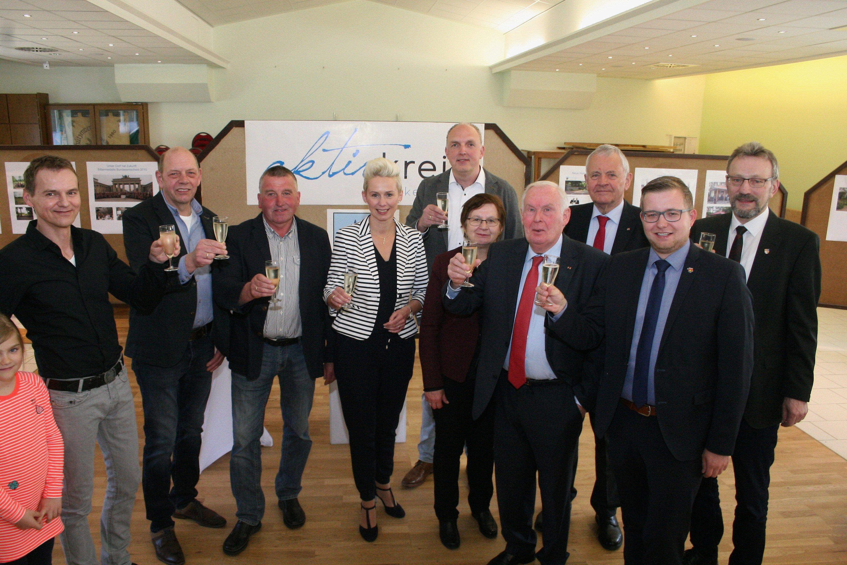 Bürgermeister Nils Anhuth stößt mit dem Aktivkreis Harkebrügge auf das Jubiläum an.