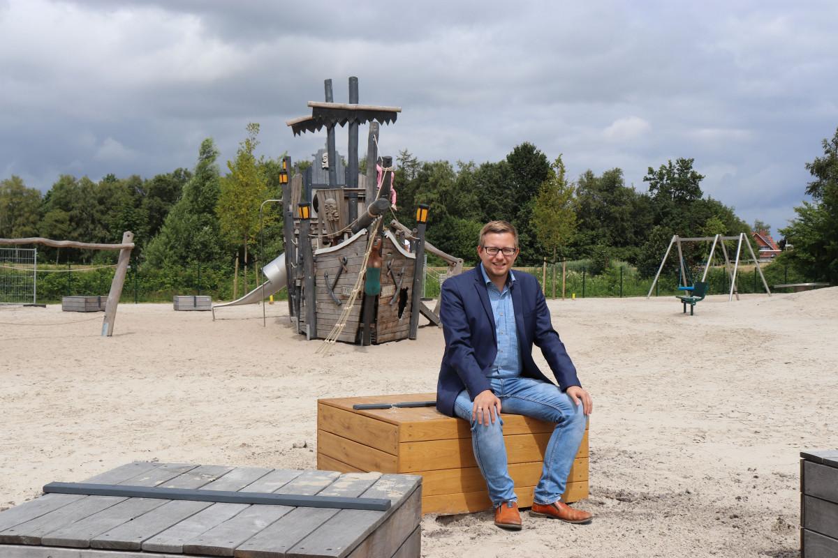 Bürgermeister Nils Anhuth testet die neuen Sitzgelegenheiten auf dem Traumspielpark.