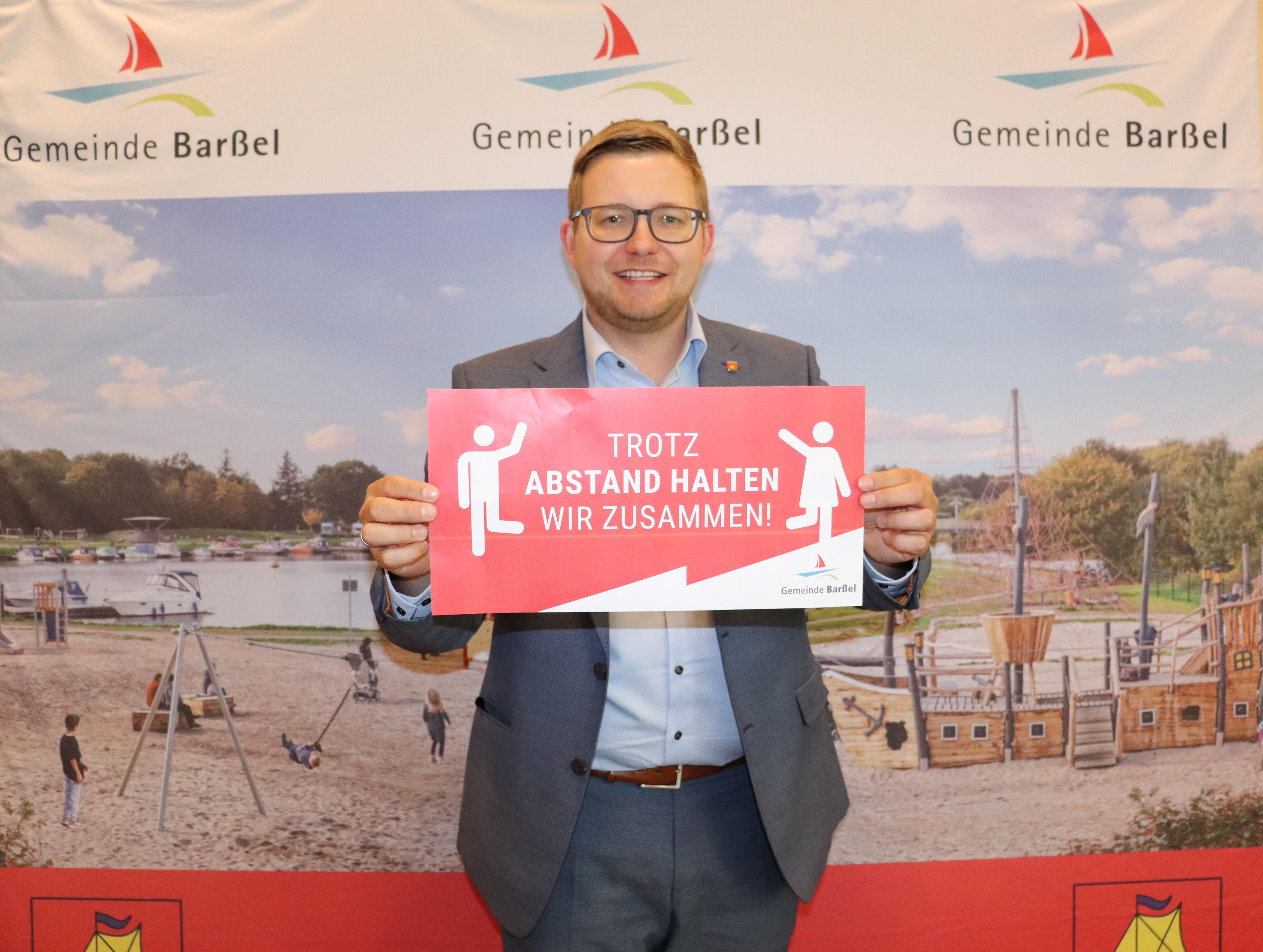 """Bürgermeister Nils Anhuth präsentiert die Aktion """"Trotz Abstand halten wir zusammen"""". Bildquelle: Wlodarczyk/Gemeinde Barßel"""
