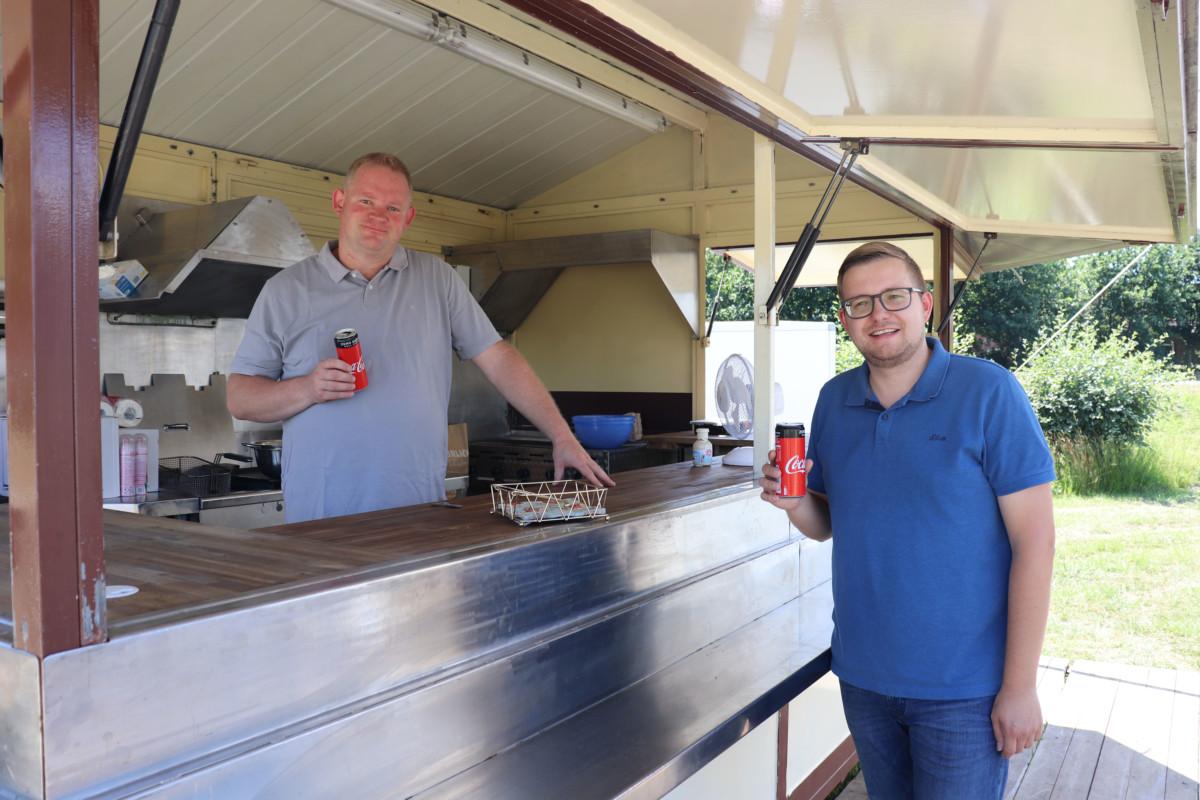 """Oswald Eilers (links) und Bürgermeister Nils Anhuth trinken beim Aufbau des mobilen """"Hafen-Cafés"""" das erste Kaltgetränk. Aufnahme: Gemeinde Barßel"""