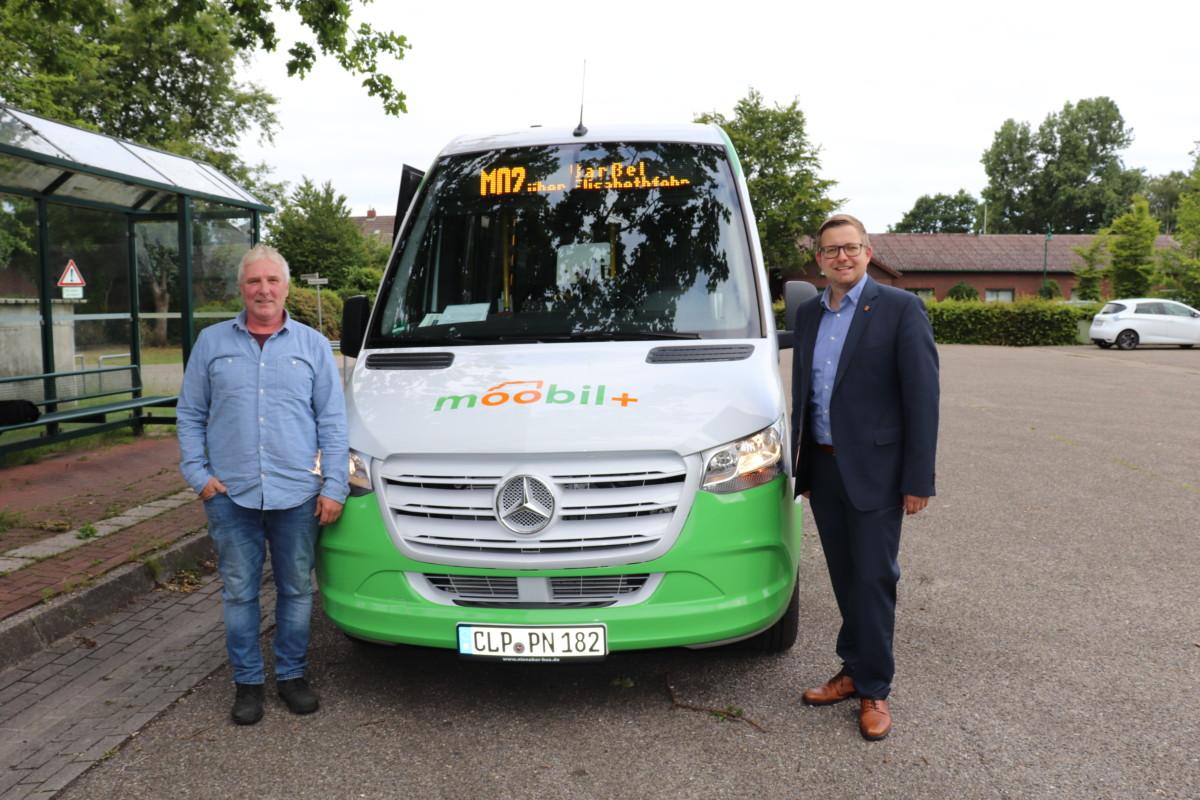 Wolfgang Böhmann (links, Fahrer des moobil+-Busses auf der Strecke in Barßel) und Bürgermeister Nils Anhuth vor dem moobil+-Bus. Bildquelle: Wlodarczyk/Gemeinde Barßel