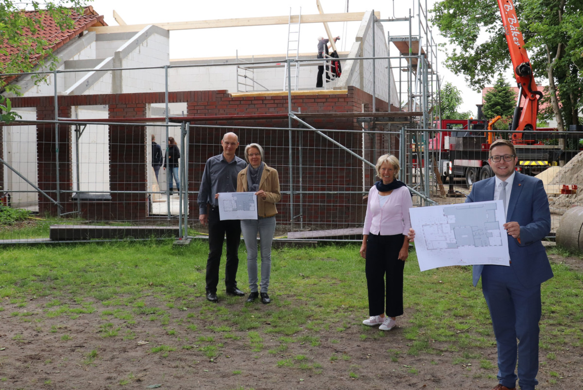 Sie freuen, sich dass der Dachstuhl im Hintergrund errichtet wird (v.l.n.r.): Thomas und Wiebke Perzul, Heike Pieper und BM Nils Anhuth. Aufnahme: Wlodarczyk/Gemeinde Barßel
