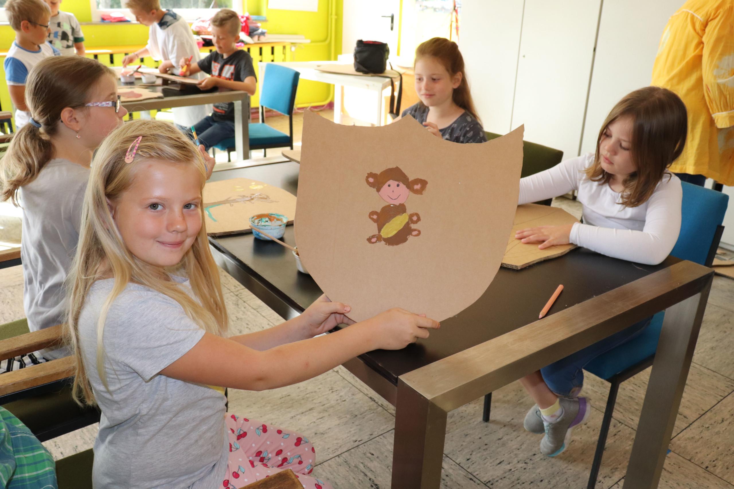 Vivien Fresenborg präsentiert stolz ihr Wappenschild mit einem Affen. Aufnahme: Gemeinde Barßel