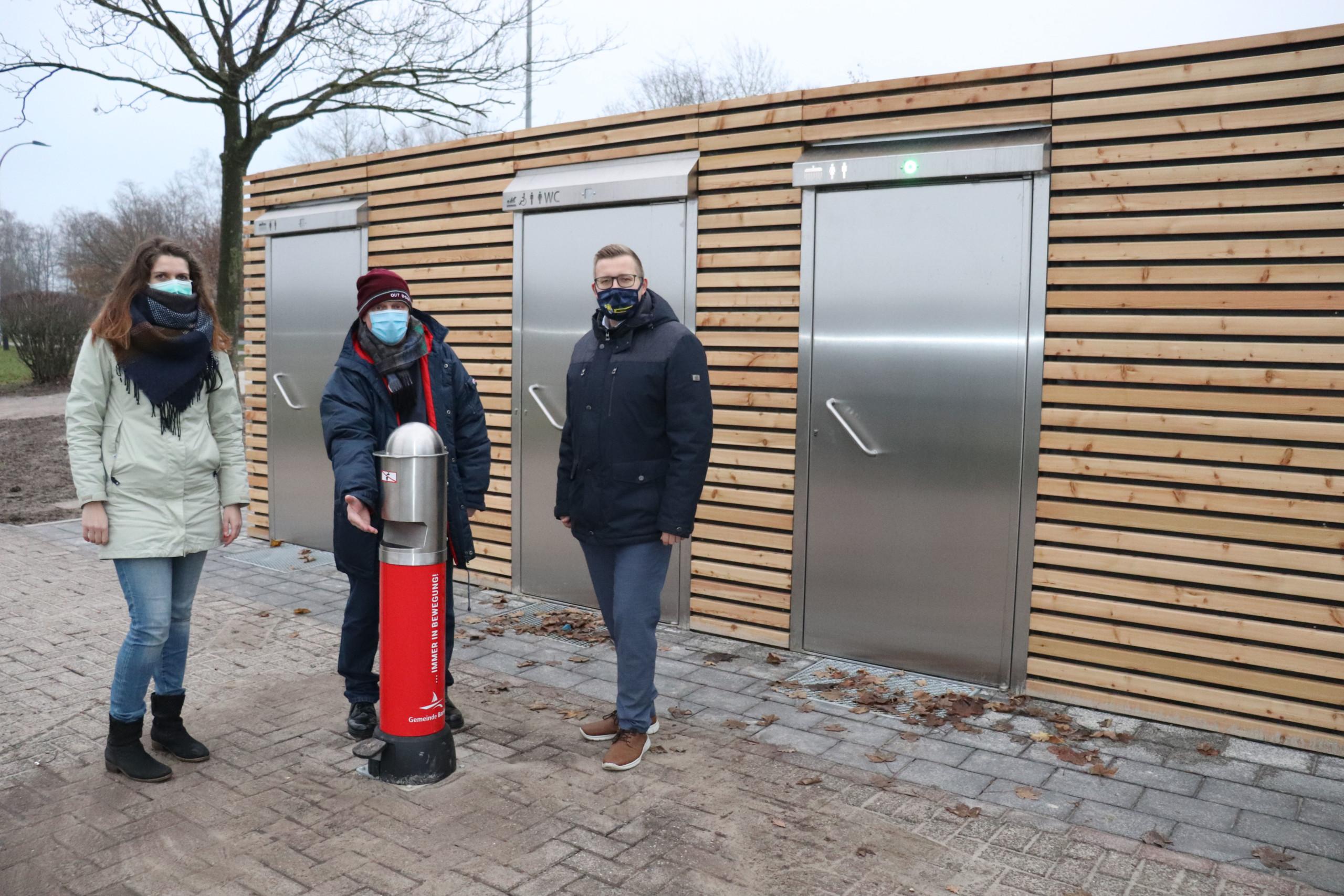 Präsentieren die neuen Containeranlagen inkl. Desinfektionsmittelspender (v.l.n.r.): Maja Peters, Hartmut Willhaus (beide vom Bauamt der Gemeinde Barßel) und Bürgermeister Nils Anhuth. Aufnahme: Wlodarczyk/Gemeinde Barßel