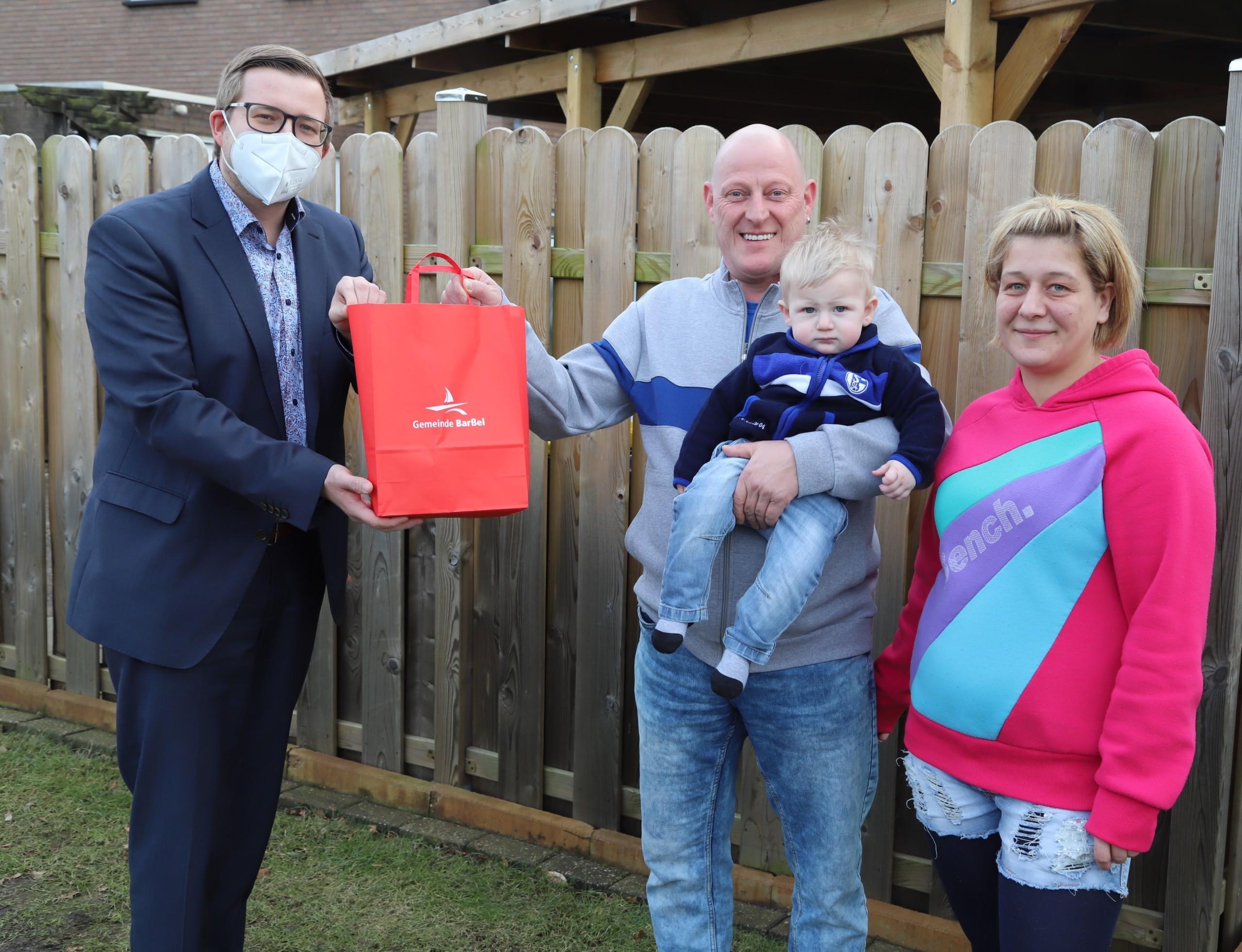 Bürgermeister Nils Anhuth überreicht Henri und Nicole Kober das Begrüßungsgeschenk für Sohn Klaus. Aufnahme: Johannes Passmann