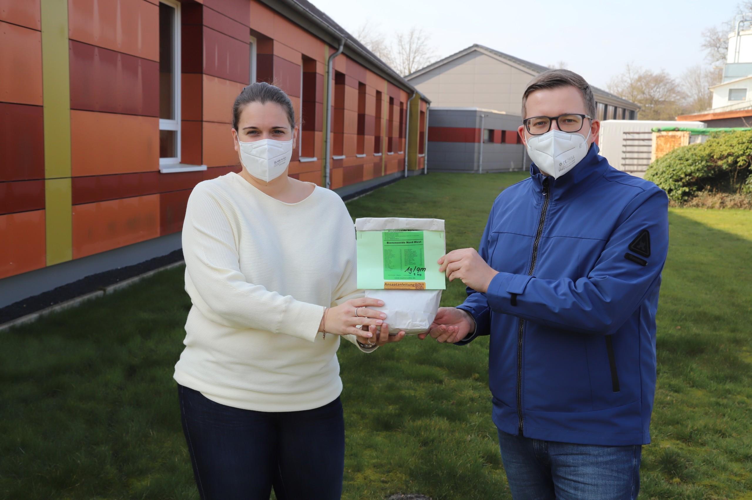 """Barßels Bürgermeister Nils Anhuth brachte eine Tüte der Mischung """"Bienenweide Nord-West"""" in die Harkebrügger Grundschule, um sie Schulleiterin Nicole Lütjelüschen zu überreichen. Bildquelle: Johannes Passmann"""
